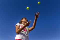 Looking up at girl juggling. Royalty Free Stock Images