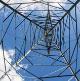 Looking up through a high voltage electrical tower. On a partly cloudy day Royalty Free Stock Photo