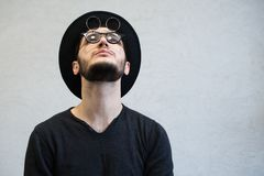 Looking up hipster man wearing sunglasses and hat. royalty free stock photography