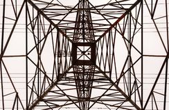 Looking up interior of large electrical tower frame. Looking up along inside of large metal electrical transmission tower frame in perspective against overcast stock photos