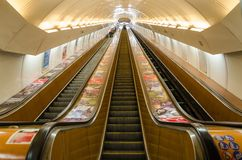 Looking up a long subway escalator with diminishing perspective in Prague stock image