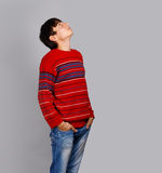 Looking up. Man in striped red sweater on grey background looking up Stock Photos