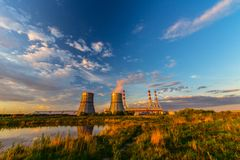 Power plant in the evening. Power plant in the sunny evening with the cloudy sky at background royalty free stock image
