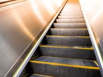 Looking up modern escalator in subway with a light from the top. stock image