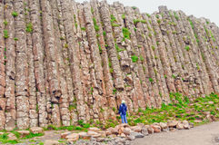 Looking up a natural Rock Wall. Person looking up at one wall of the Giant's Causeway in Northern Ireland Royalty Free Stock Photos