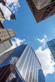 Looking Up New York. Looking up at skyscrapers in Manhattan with a blue sky and clouds Royalty Free Stock Image