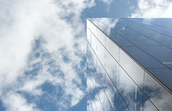 Looking up at reflections on glass covered corporate building Royalty Free Stock Images