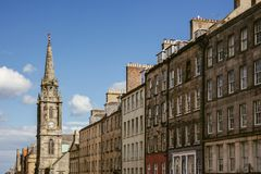 Looking up at a row of houses and church steeple in an Edinburgh. Scotland street on a beautiful sunny day Stock Images