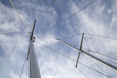 Blue sky above the yacht. Looking up at sails and mast of boat / yachting Royalty Free Stock Photos