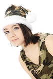 Looking Up in Santa's Camoflauge. Close-up of a beautiful teen girl looking up.  She's dressed in a camouflage Santa hat and sleeveless shirt.  On a white Royalty Free Stock Image