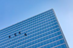 Four Window Washers on the Side of a Skyscraper royalty free stock photography