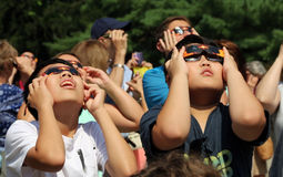 Looking Up At The Solar Eclipse. A group of children looking up at the 2017 solar eclipse, using protective glasses at the Livingston Library terrace in Royalty Free Stock Photos