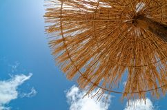 Looking up at the straw parasol and the blue sky. This scene was taken on the sandy beach on Sal in Cape Verde. Looking up at the straw parasol and the blue sky royalty free stock image