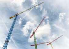 Looking up at three colorful cranes Stock Images