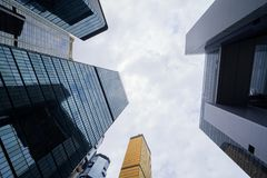 Looking up to high-rise buildings, skyscrapers, architectures in smart city for business and technology background in Hong Kong. City with blue sky stock image