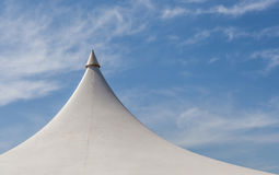 Looking up at the top of white tent against beautiful blue sky. Stock Photo