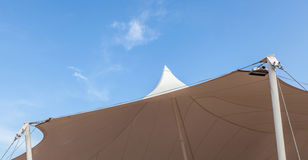 Looking up at the top of white tent against clear blue sky backg Stock Image