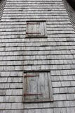 Looking up the wall. Two boarded windows against a weathered wood shingle siding Royalty Free Stock Images