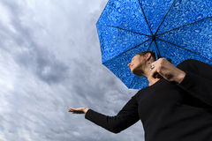Looking up at woman holding umbrella and dark clouds Royalty Free Stock Image