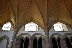 Looking up at the wooden patterned ceiling inside a church. Rows of columns under the small windows which are letting some light into the church and a decorative royalty free stock photos