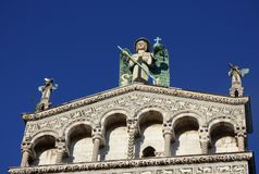 Looking upward at the facade of a cathedral with angelic statues and a blue sky background stock photos