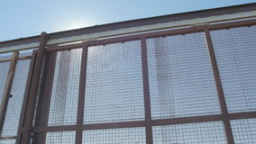 Looking at the US and Mexico Border Fence from Side to Side. Pan shot of the US and Mexico border fence from one side to the other in 4K on a sunny day stock footage