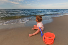 Looking on waves. Chid  on the beach watching the sea Stock Images