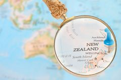 Looking in on Wellington, New Zealand. Blue tack on map  with magnifying glass looking in on Wellington, New Zealand Royalty Free Stock Photos