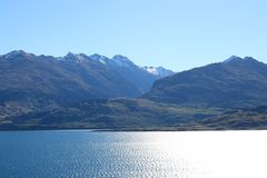 Up sun across Lake Wanaka to mountains New Zealand. Looking West across Lake Wanaka from Lake Wanaka lookout on state highway 6 near The Neck to snow capped stock image