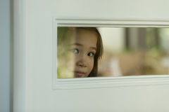 Looking through a window. Girl playing peek-a-boo through a kitchen window in a door Royalty Free Stock Photos