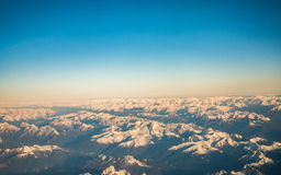 Looking through the window aircraft during flight a snow covered Italian and Osterreich. Alps with blue sky without clouds Royalty Free Stock Images