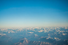 Looking through the window aircraft during flight a snow covered Italian and Osterreich. Alps with blue sky without clouds Royalty Free Stock Photography