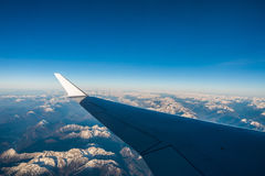 Looking through the window aircraft during flight a snow covered Italian and Osterreich. Alps with blue sky without clouds Royalty Free Stock Photos