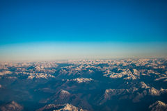 Looking through the window aircraft during flight a snow covered Italian and Osterreich. Alps with blue sky without clouds Stock Photos