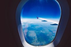 Looking through window aircraft during flight in wing blue sky Royalty Free Stock Photo