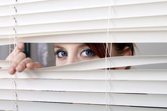 Looking through the window blinds. Suspicious blue eyed redhead woman peeking through the white window blinds stock images