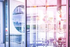 Looking through window of empty restaurant on river and modern a. Rchitecture Stock Photo