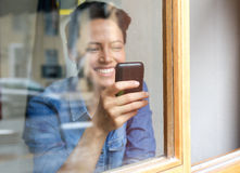 Looking through window at smiling young woman using cell phone Royalty Free Stock Images