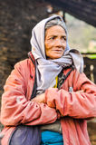 Looking woman in Nepal. Dolpo, Nepal - circa May 2012: Old woman with wrinkles and with grey headcloth wears pink jacket and looks to right in Dolpo, Nepal Stock Image