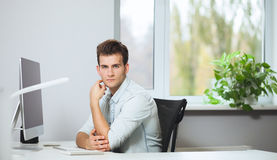 Looking from the working men in the office. Stylish designer at work sitting. Focused on his job royalty free stock image