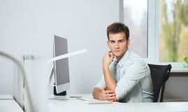 Looking from the working men in the office. Stylish designer at work sitting. Focused on his job stock photography