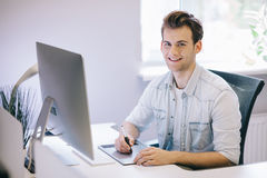 Looking from the working men in the office. Stylish designer at work sitting. Focused on his job stock image
