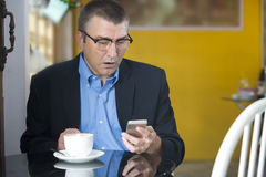 Looking worried while reading on his cellphone Royalty Free Stock Images