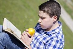 Looking.Young mens die een boek in openlucht met gele appel lezen. stock foto's