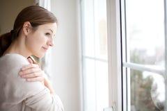Lookong de la mujer de una ventana de su casa fotos de archivo libres de regalías