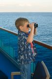 The Lookout. A young child scans the ocean horizon while on a tropical cruise Stock Image
