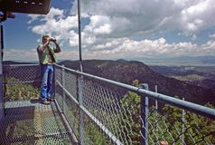 Lookout in fire-tower. Lookout in tower glassing the Gila national forest from the continental divide for wildfires after a thunderstorm stock photography