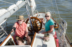 The Lookout. A senior couple sail on their classic ketch as he points to indications of wind on the water ahead while she steadies the helm Royalty Free Stock Photography