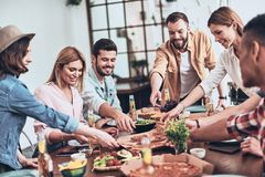 Looks delicious. Group of young people in casual clothing picking pizza and smiling while having a dinner party indoors royalty free stock photography