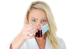 Looks good... Young blond woman in white chemist uniform and face mask holding red liquid in hand Stock Photos